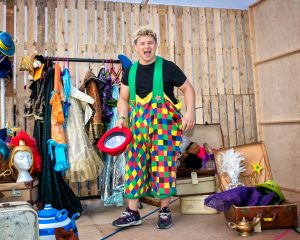 Josh Benson in colourful panto costumes smiling at the camera